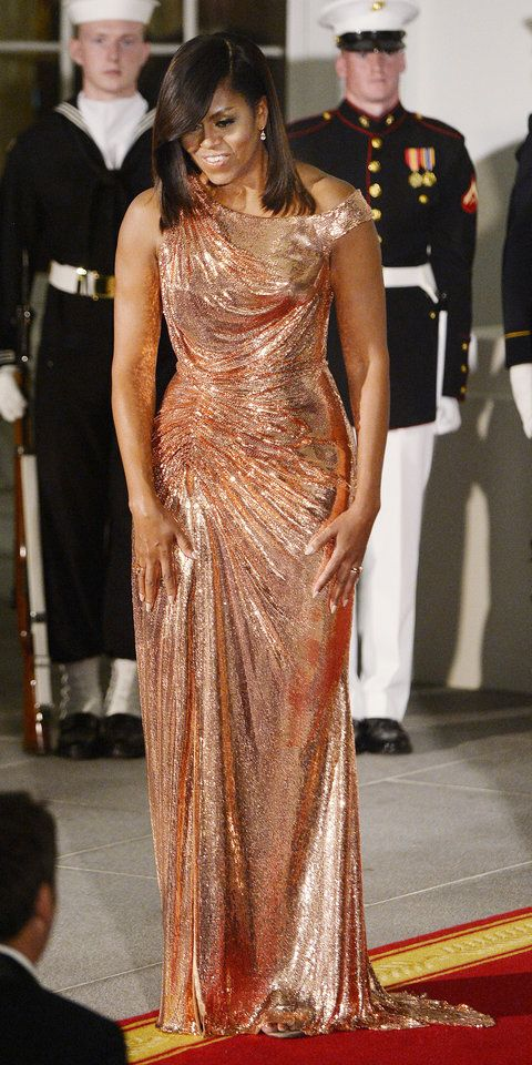 For her final State Dinner, Michelle Obama pulled out all the stops, making a show-stopping entrance in a custom rose gold Atelier Versace chainmail gown wit  a fitted bodice, drapery, and an asymmetric off-shoulder neckline, styled with Le Vian diamonds.