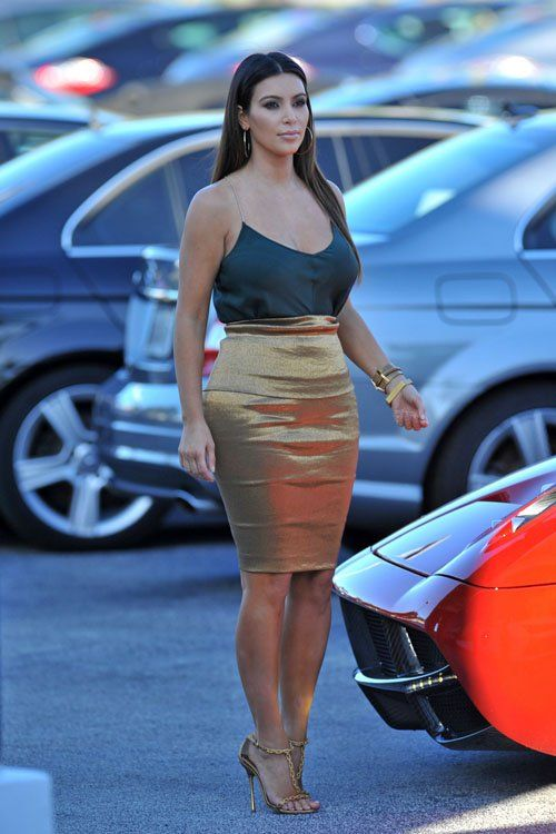 Kim Kardashian wearing Tom Ford Spring 2012 Sandals and Donna Karan Gold Fold Over Skirt.
