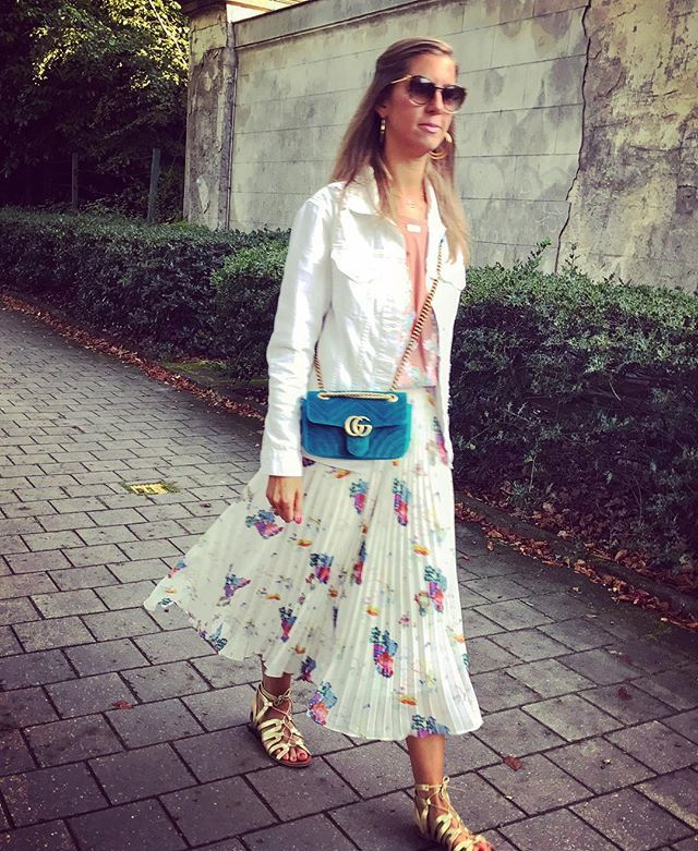 Isabelle is wearing a pleated skirt and golden sandals by & Other Stories and a blue velvet Gucci bag.