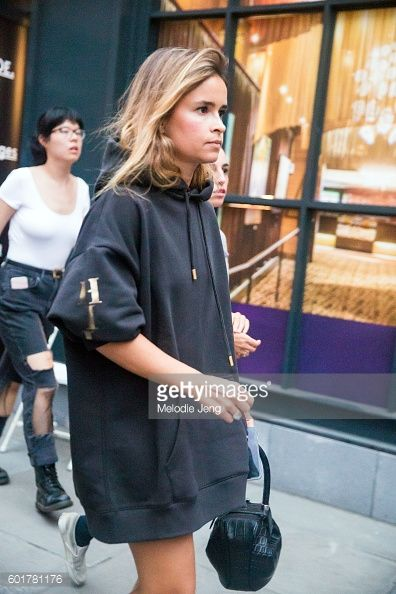 Miroslava Duma wears an oversized black hoodiedress and black Gabriela Hearst bag at the Tommy Hilfiger x Gigi Hadid show at Tommy Pier on September...