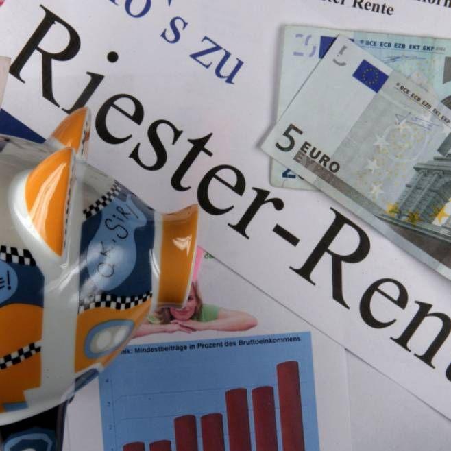 Ein Sparschwein steht auf einem Werbeträger mit der Aufschrift Riester-Rente