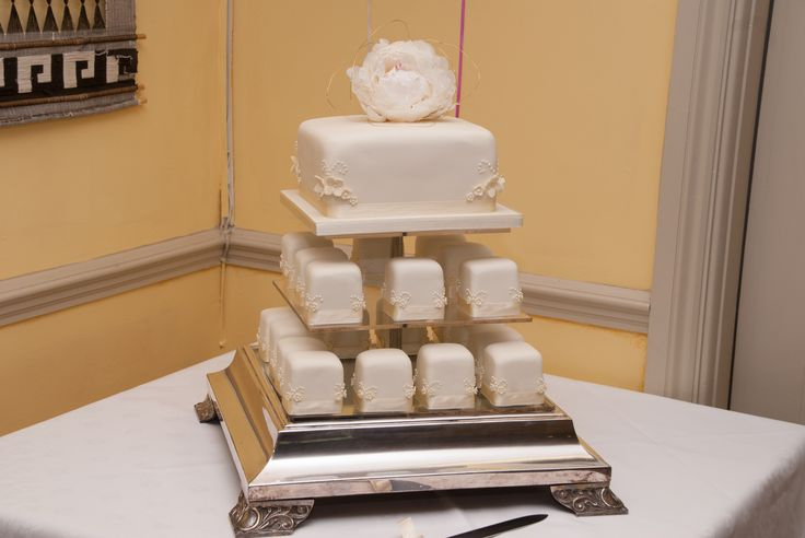 Three tier square wedding cake with mini cupcakes.  Fresh flower topper.