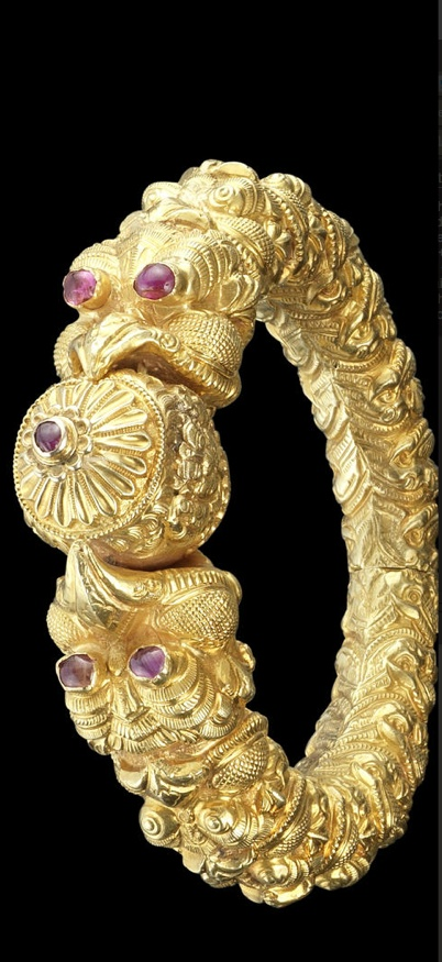 A ruby-set repousse gold Bangle   Madras, 19th Century  hinged, the terminals in the form of makara heads with mouths open holding a floral bud, the eyes and bud set with rubies, the tapering sides with a series of makara heads