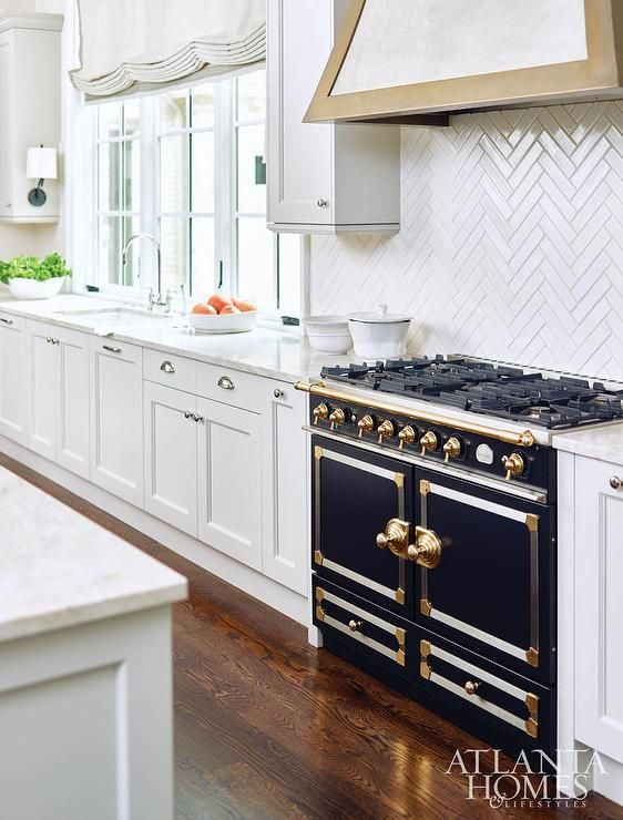 Glam kitchen features white shaker cabinets adorned with shiny nickel cup pulls paired with white marble countertops and a thin, white herringbone tile backsplash that only goes up half the wall lined with a white and gold French range hood and a black and gold French stove, La Cornue Range.