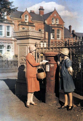 "Two girls send a letter at the red ""pillar box"" of the Royal Mail. Belfast, Ireland, 1920's, National Geographic."