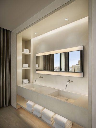 Mooi ontwerp van dubbele wasbak in soort nis tussen 2 muurtjes, met ingebouwde nis aan binnenkant en ingebouwde verlichting. Mooie extra legruimte onderste plank.