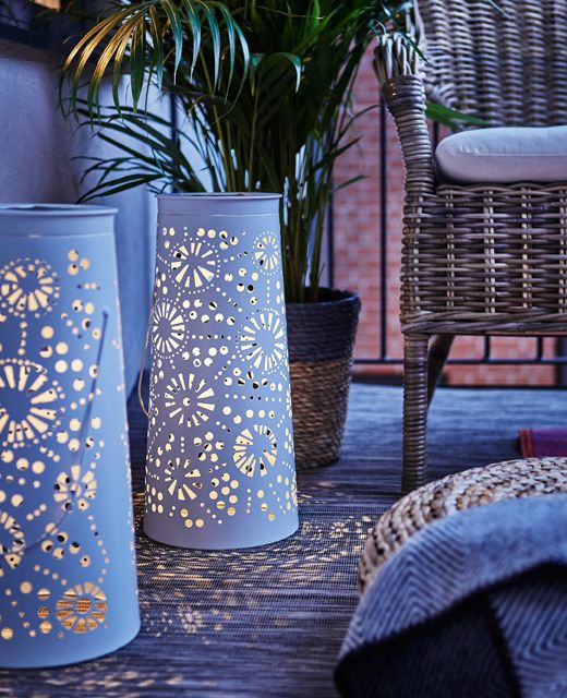 Two decorative, metal, solar-powered lanterns light the balcony during the evening.
