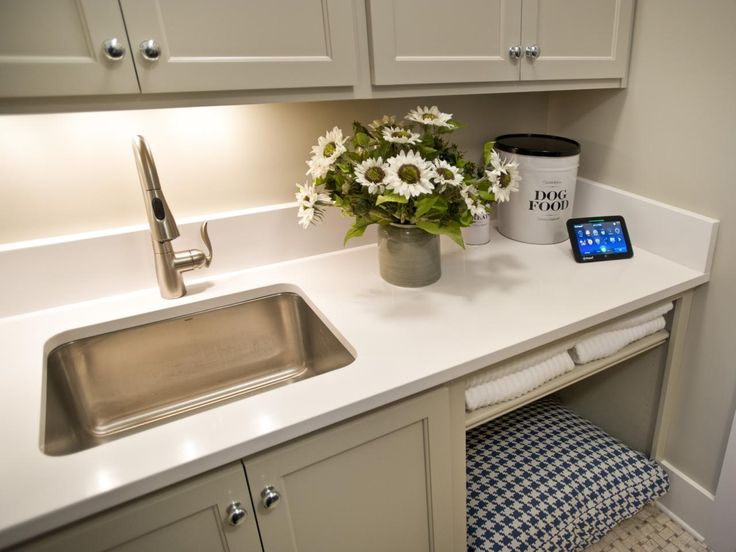 Sophisticated gray cabinetry and clever nooks offer ample space for cleaning supplies and pet-friendly amenities in the laundry room of the HGTV Smart Home 2014. An undermount sink and white countertops are stylish and hard-working, making any household chores a breeze.