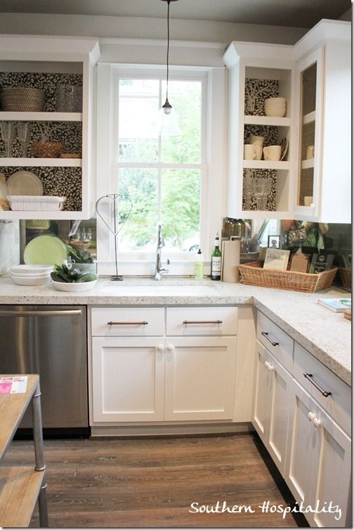 Fabric covered cabinet backs and thick open shelving make for lovely storage in this kitchen.
