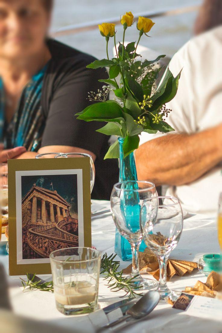 A vendégasztalok unalmas számok helyett városok neveit kapják, melyet az asztalközepre helyezett aranykeretes kép szimbolizál. Jól mutatnak a karcsú türkiz vázákban aprófejű sárga rózsák.