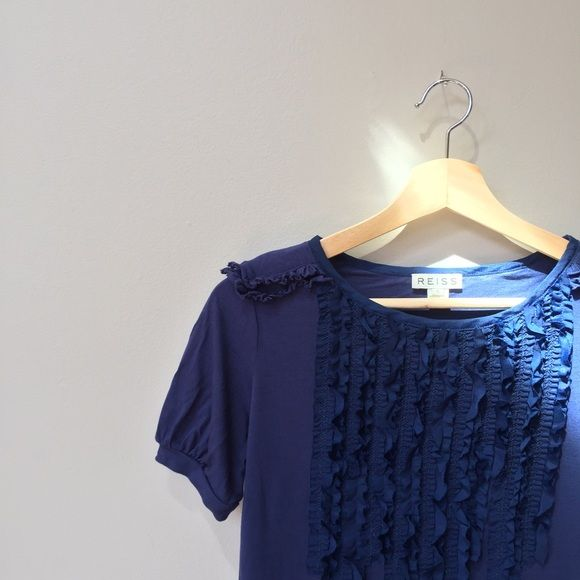 Buttery Soft Reiss Indigo Ruffle Top Reiss Blue Indigo Raw Edge Technique Top 🔹 FALL 2016 TREND WATCH: romantic ruffles, military shoulder detail. 🔹 Feels like the softest T-shirt in your closet -- we're talking ultra buttery soft -- but the pretty ruffle details make this ready for work or a night out.  🔹 From iconic UK brand Reiss, worn by Kate Middleton.  🔹 Originally $105 retail. Gorgeous indigo color. 100% viscose.  🔹 Excellent condition. 🔹 Offers encouraged! 🔹 20% off if…