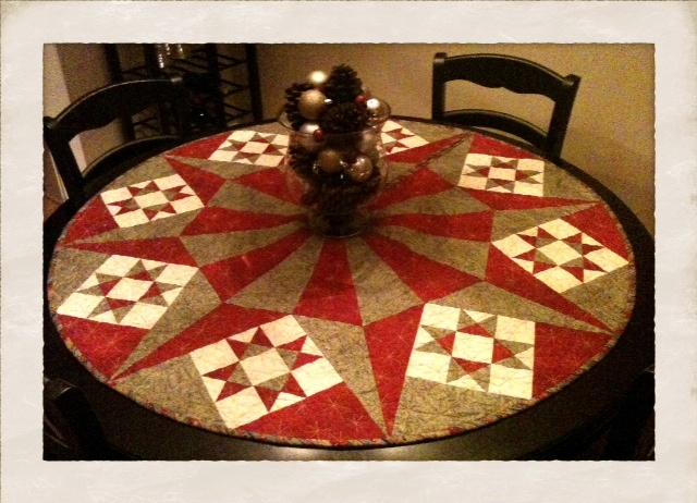 Handmade Quilted Tree Skirt Used As A Table Centerpiece. Vase With Cinnamon  Scented Pine Cones