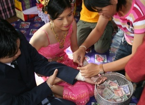 A Thai village wedding everybody ties 'magic string' around the wrists of the couple to bring them luck and the pot of money gifts.  Money is important.  The groom's family have to pay a 'bride price' to the bride's family and this reflects the value of the bride and the wealth of the groom.  Visit our guest house  http://thailand-painting-holidays.com #painting #holiday #thailand #travel #vacation #photography #culture https://plus.google.com/u/0/104359568476968412848?rel=author