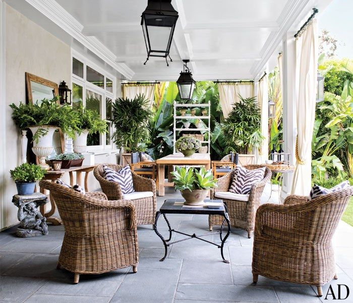 A terrace featuring wicker club chairs and a vintage French Art Deco iron table | archdigest.com