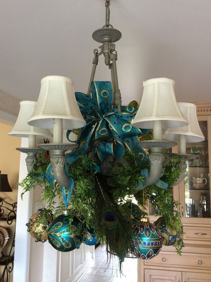 Peacock decorated chandelier carries theme over dessert table. Ribbon from Hobby Lobby, green plastic vine from Michaels, ornaments and peacocks from my Christmas tree decorations.