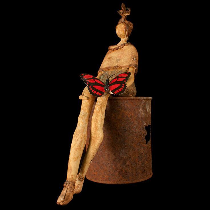 Mujer con mariposa sentada en una lata oxidada. Escultura cerámica.