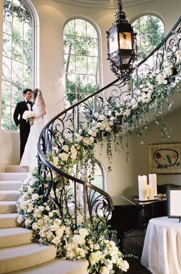 dramatic florals surrounding a round staircase at Black Tie Secret Garden Wedding