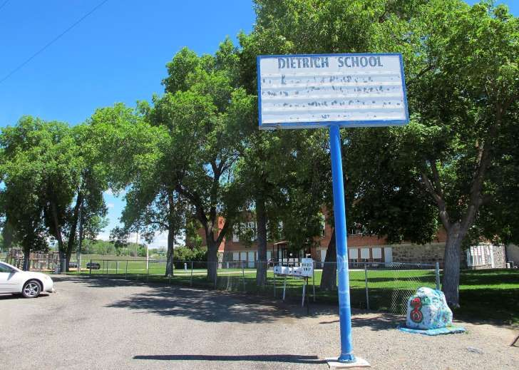 In this Thursday, May 26, 2016 photo, an empty school reader board stands in front of the only school building in Dietrich, Idaho. The small community is struggling with the national attention brought by reports that a disabled black football player was raped by his white high school teammates. The allegations of racist taunts and physical abuse suffered by the teen were revealed this month when the family filed a $10 million lawsuit against the Dietrich School District. (AP Photo/Kimberlee…