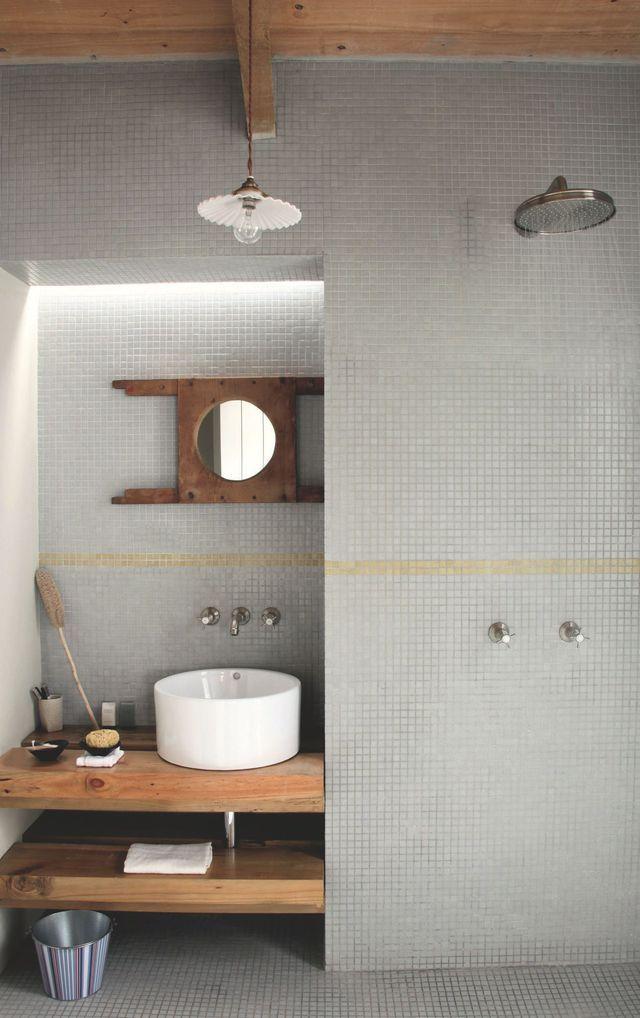 La salle d'eau est entièrement carrelée de mosaïque et soulignée d'une ligne jaune. Au-dessus du lavabo, la structure entourant le miroir est un ancien siège de toilettes en bois provenant d'un collège du Cap