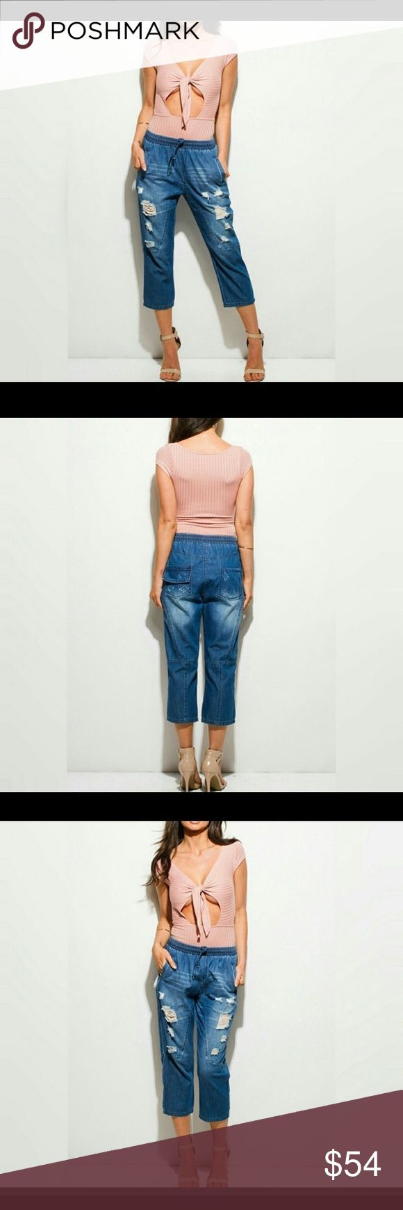 Distressed Cropped Joggers Medium wash 100% cotton light weight denim cropped jeans, elasticized drawstring waist, diagonal pockets, loose fit, factory distressing, runs on the smaller side Jeans Ankle & Cropped