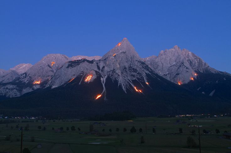 "The mountains of the Zugspitz in Ehrwald, Austria were the canvas this past Saturday, June 21, illuminating photos of Jesus, crosses, flowers and animals. The lighting of fires, ""Bergfeuer"" on the mountains at summer solstice is an ancient custom in the Alpine region, which has survived to this day."