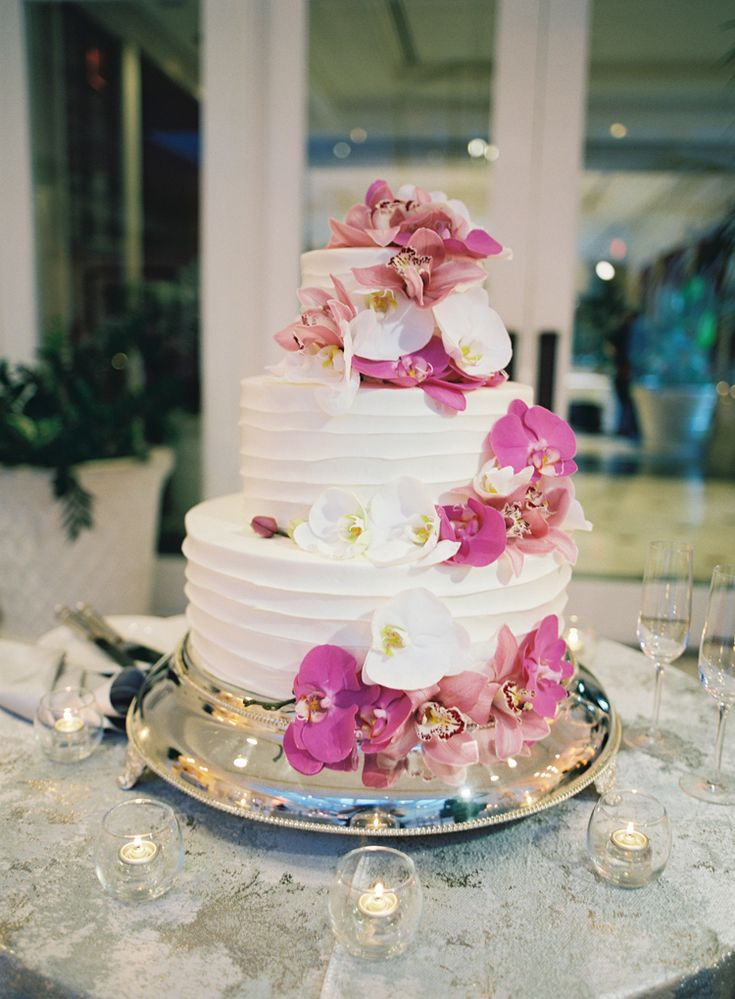 Gorgeous three tiered wedding cake with white and purple orchids  (Virgil Bunao)