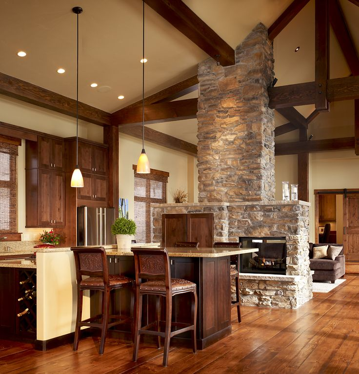 Walnut cabinets with light countertops, cool timberwork and stone fireplace.