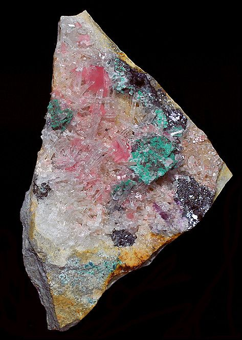 Colorful specimen of Rhodochrosite with Quartz, Tetrahedrite, and Malachite!  As far as I know, only one pocket with Malachite was found at the Sweet Home Mine.  Most specimens from there had poor quality Rhodo in pretty rough shape. This was the  only specimen I found that had several complete and gemmy rhombs with the Malachite!  From the Malachite Pocket, 3rd Tetrahedrite Raise, Sweet Home Mine, Alma, Colorado.  Measures 8.5 cm by 5.5 cm in size.