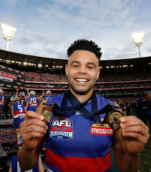Jason Johannisen of the Bulldogs holds his Norm Smith and Premiership medals after the 2016 AFL Grand Final match between the Sydney Swans and the...