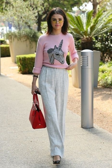 Selena Gomez In a Coach pink unicorn sweater, grey trousers, a red Coach handbag, black patent leather pumps, and yellow-tinted sunglasses while out in LA. #sunglasses #fashion #style #outfit #selenagomez #hair #celebrity