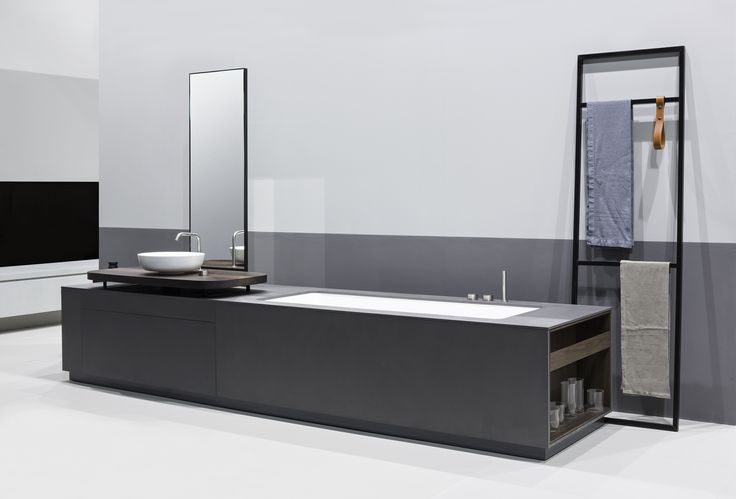MANHATTAN is a Bathtub Washbasin system for the bathroom in grey eco-cement, characterized by a clear and rigorous geometric sign with dark nuances and displaying an innovative console in smoked oak with a soft and fluid shape. The refined graphic combination of lines and geometries are highlighted by the vertical mirror, the OX taps in stainless steel 316L, the sequence of claddings and full and empty spaces of the open racks.