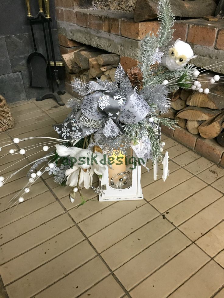 Lantern swag - winter. In the colors white-silver-grey. Full of evergreen branches, funky bow, owl, bird, snowflakes, pinecones and handmade garland with sledge. With LED candle with timer.