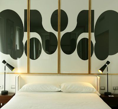 Love the low, winged upholstered bead head and statement gold framed black and white art.