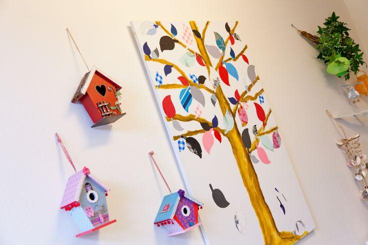 Creatieve muur met zelfgemaakte vogelhuisjes en kleurrijke boom van papier.