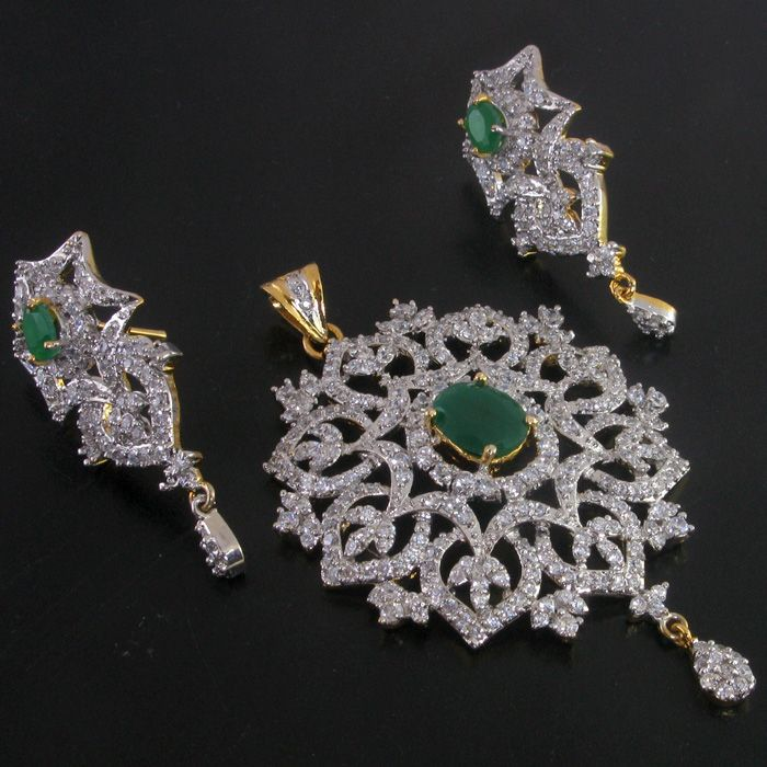 This exquisite piece of jewellery is made of Two tone and is studded with the finest CZs and Simulated Emerald.This set features a beautiful pendant and earrings,  which has so much sparkle that you would feel like a princess18 ct Gold and platinum polish, handcrafted with high quality American Diamond CZsPendant measures : Length (approx) - 75mm x 45mm or 3