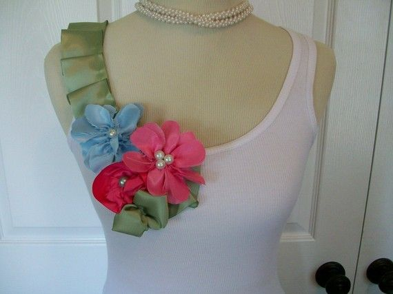 This pretty ribbed white tank top is adorned with sage ruffles and beautiful flowers with pearls in the center. It have a gorgeous leaf accent on