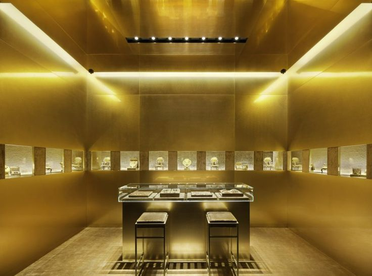 The large staircase and a small room for fine jewellery collection are finished with gold-coloured walls and brass fittings – including a brass ceiling and gold-toned carpet in the jewellery area – to contrast with the rest of this Dolce & Gabbana store.