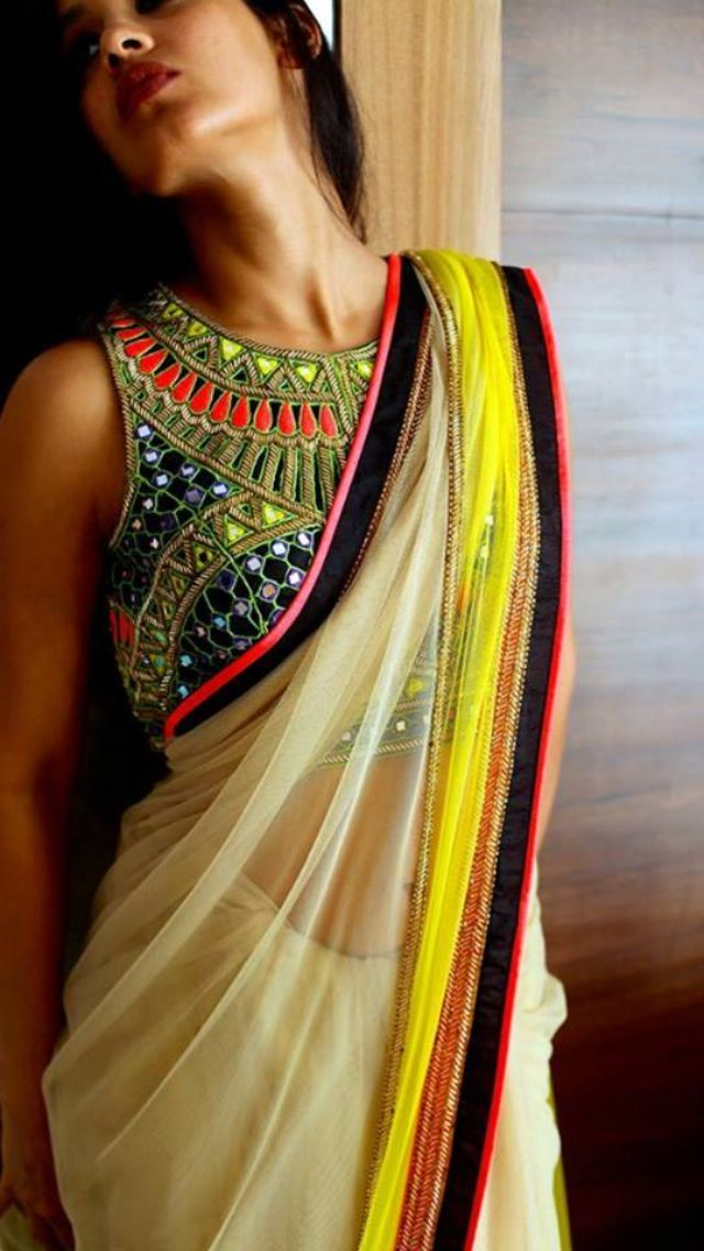 This sleeveless blouse designed by Arpita Mehta has intricate embroidery consisting of vibrant anchor threads and mirrorwork. Related PostsBlack Kashmiri Work Half and Half Saree by Tarun TahilianiCut Work Blouse by Designer Anand KabraRed Zari Border Saree from SejalKanoiBlack Cut Work Sleeveless BlouseBeautiful Magenta Lehenga from Anita DongreZemanta