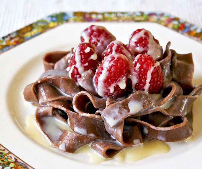 Chocolate Pasta with White Chocolate Liqueur Sauce - a different yet delightfully chocolatey dessert topped with luscious raspberries.