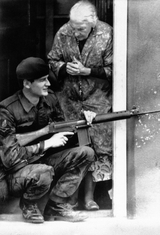 An old woman, a rosary dangling from her neck, clasps her hands on finding a British Army sharpshooter on her door step in Belfast's market area as troops flushed out snipers barricaded in bakery in Northern Ireland capital on August 11, 1971. (AP Photo)