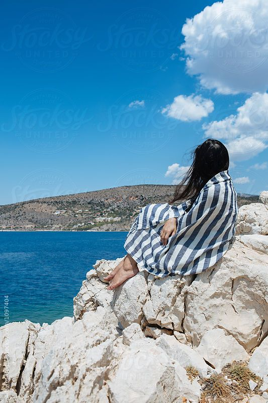 Side view of young woman wrapped in striped blanket and sitting on white rocks at Greek sea against of blue sky.Peloponnese,Greece.