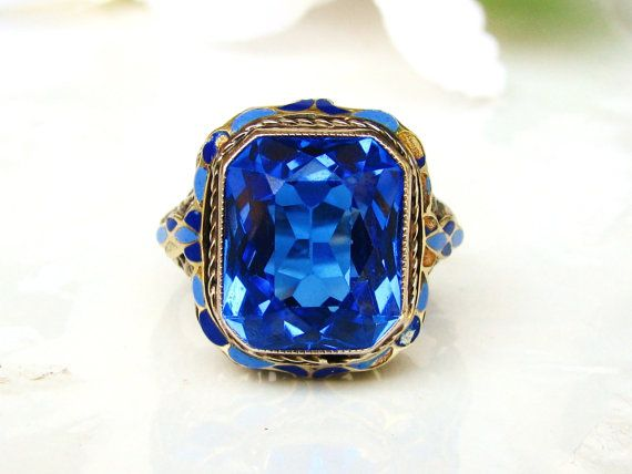 An antique Art Deco engagement ring crafted with a synthetic royal blue spinel, artfully crafted of enamel accents, 14k white gold and floral detailing that is just stunning! The beautifully faceted synthetic blue spinel is emerald shaped measuring approximately 11mm long x 9mm wide or 5.21ct with some minor surface wear noted. The stone is bezel set trimmed in mil grain on the white gold filigree setting with floral blossom details placed on the east/ west sides with pretty decorative…