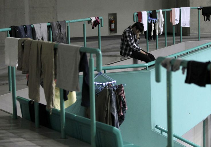 An evacuee, who fled from the vicinity of Fukushima nuclear power plant, sits next to laundry hanged out to dry at an evacuation center set in a gymnasium in Yamagata, northern Japan March 18, 2011. REUTERS/Yuriko Nakao