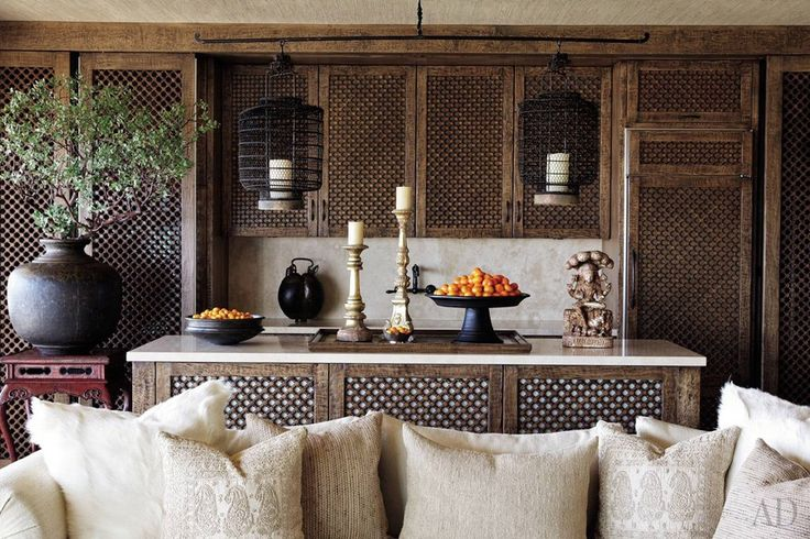 Asian and Middle Eastern influences inform the interiors Martyn Lawrence Bullard conceived for Cher's Los Angeles duplex. Although the singer and actress insisted on a neutral palette, the designer used intricate detailing and bold accent pieces to enliven the home. In the open kitchen, hand-carved screens cover the cabinets and conceal state-of-the-art appliances, while Chinese hanging lanterns add to the exotic atmosphere. (July 2010)
