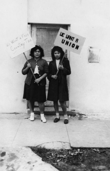 """Rosie Albrann and Ramona Fonseca are part of a long women's labor and fashion history that extends back to the turn of the 20th century. These garment workers are from the Barenveld Shirt Factory in San Fernando, California (ca. 1943). Their placards read: """"We want a union."""" and """"We want a free country too."""""""