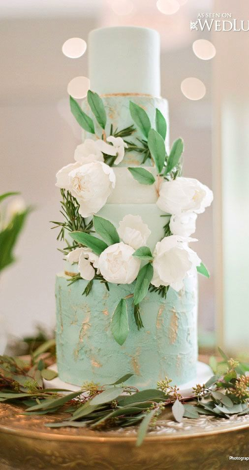 Mint-colored wedding cake adorned with greenery