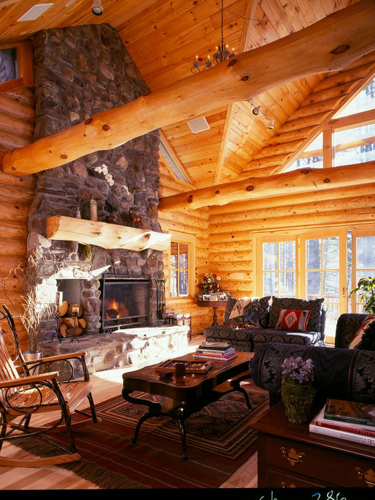 A Stone Fireplace And Decorative Log Beams Add Interest To This Log Home  Living Room.