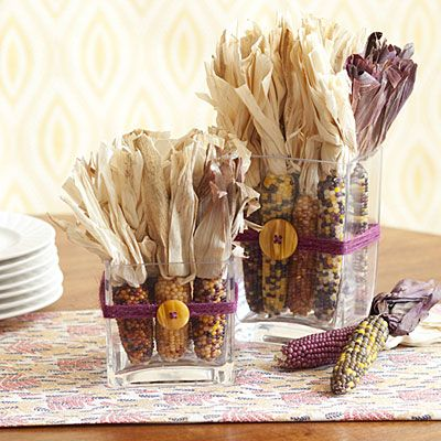 "Thanksgiving Table Decorations: Harvest centerpiece...Hail the Harvest  ...""Colorful ears of dried Indian corn are so beautiful they need only a little adornment to make a striking centerpiece. Find them at a farm stand or order them online (ecklerfarms.com). Arrange them in a glass vessel and trim the husks to a uniform height. Thread twine through a button and wrap around the vessel; tie in a knot to secure."""