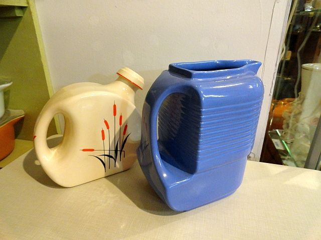 """Two late-1940s ceramic water jugs. On the left, a Sears Roebuck with cork-lined ceramic stopper in the """"Cat Tail"""" pattern. On the right, a Hall for Westinghouse pitcher in delphinium blue. Both in excellent condition! Available now at the Vancouver Flea Market. https://www.facebook.com/Gleaner84"""