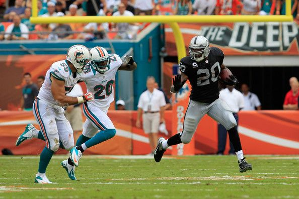 (R) Darren McFadden #20 of the Oakland Raiders is pursued by Reshad Jones #20 of the Miami Dolphins and Koa Misi #55 of the Miami Dolphins at Sun Life Stadium on September 16, 2012 in Miami Gardens, Florida.